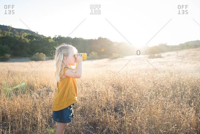 Little girl standing in a field looking through toy binoculars