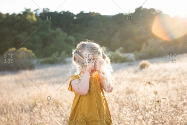 Little girl standing in a field covering her face with her hair