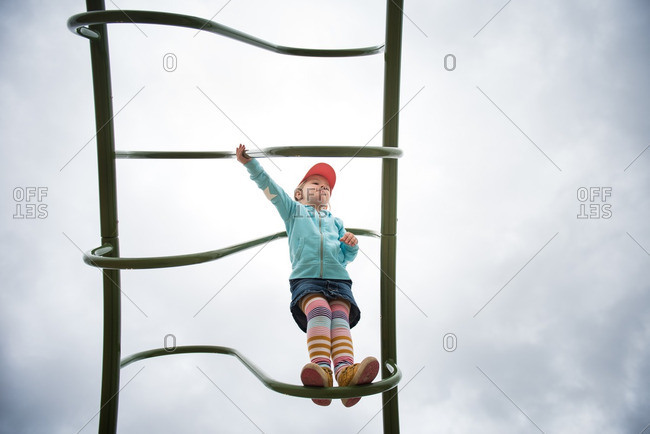 Little girl climbing on curved rungs of a playground ladder