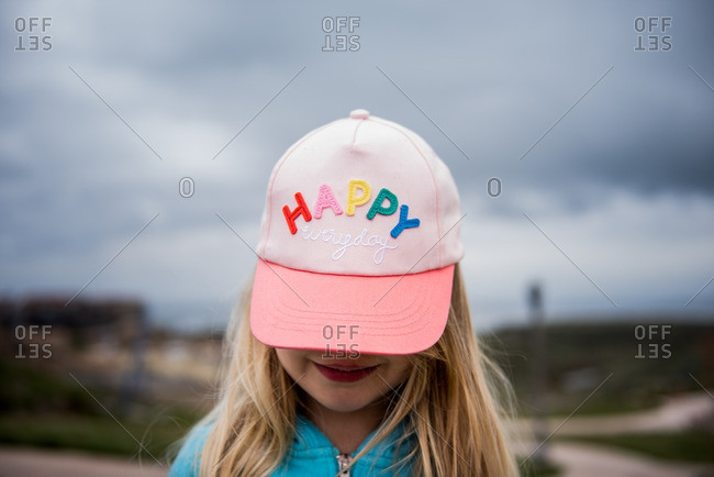 "Little girl wearing a baseball cap that says ""happy"""