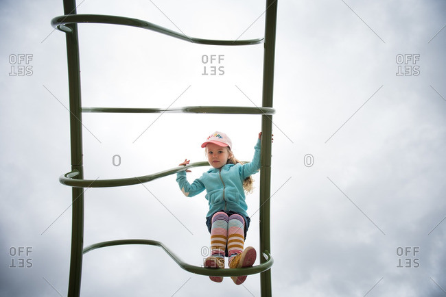 Little girl climbing on a ladder at a playground