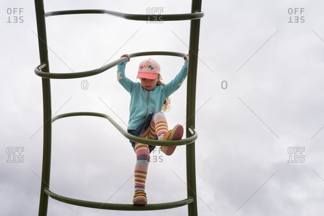 Girl climbing on the curved rugs of a playground ladder