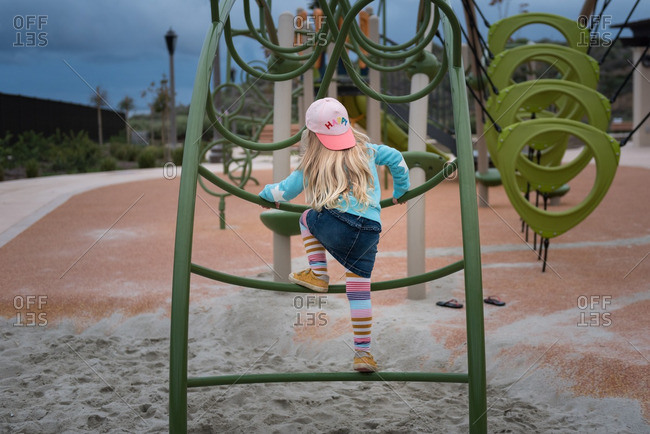 Little girl in a backwards cap climbing on playground equipment
