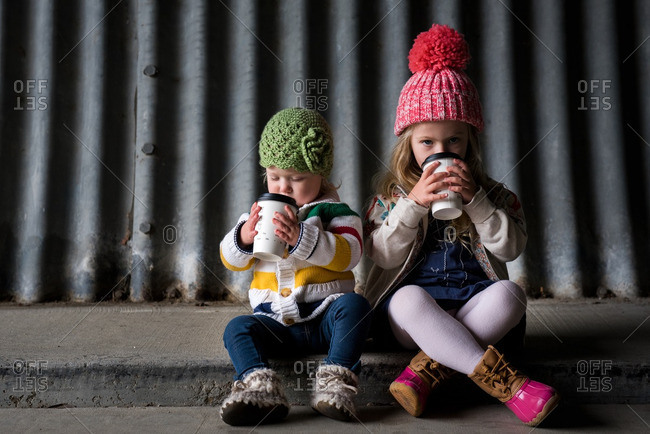 Two sisters in toboggans sitting on a sidewalk drinking warm beverages