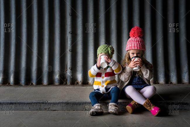 Two sisters sitting on a sidewalk in toboggans drinking warm beverages
