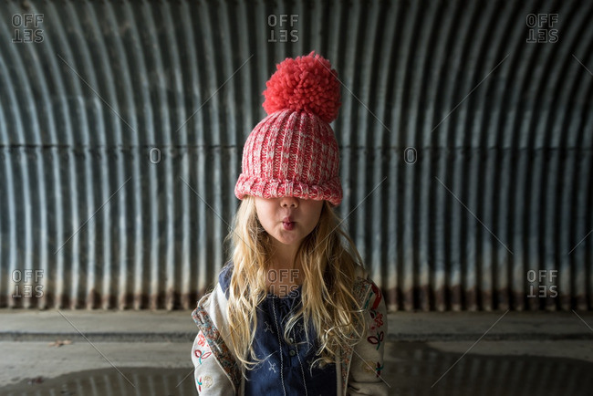 Little girl in a toboggan standing in a tunnel pursing her lips
