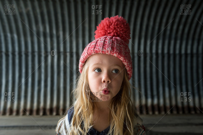 Little girl in a toboggan standing in front of a corrugated metal wall