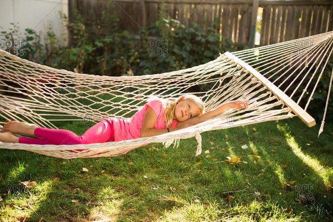 Little girl lying in a hammock in a backyard daydreaming