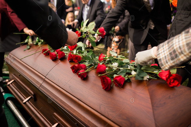 People placing roses on top of a casket at a funeral