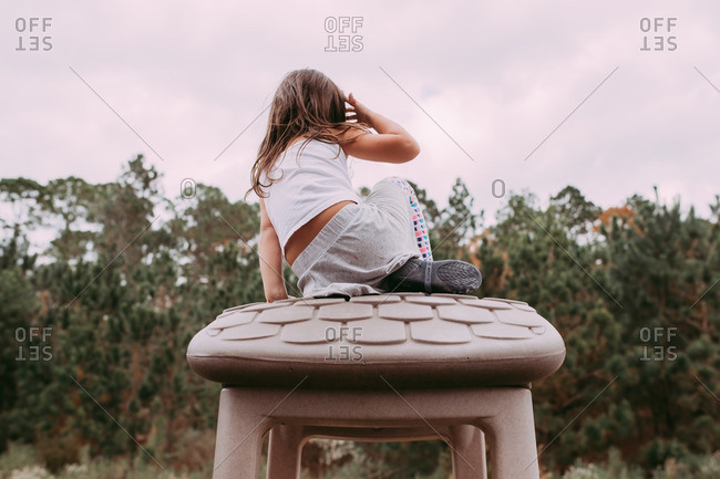 Young girl climbing on top of toy house