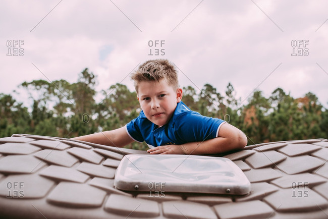 Boy climbing on roof of toy house