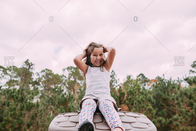 Smiling girl sitting on top of toy house