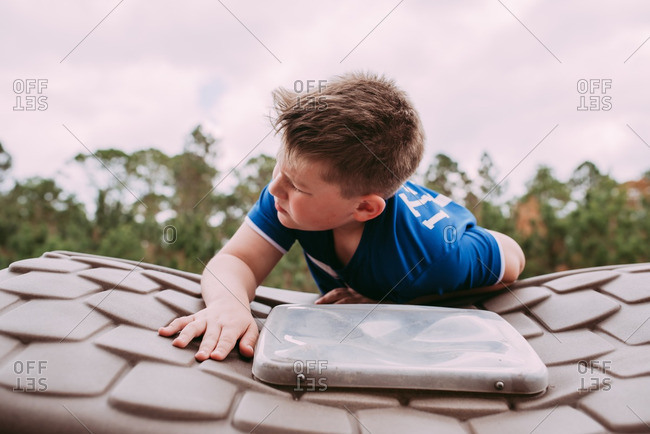 Young boy climbing on roof of toy house