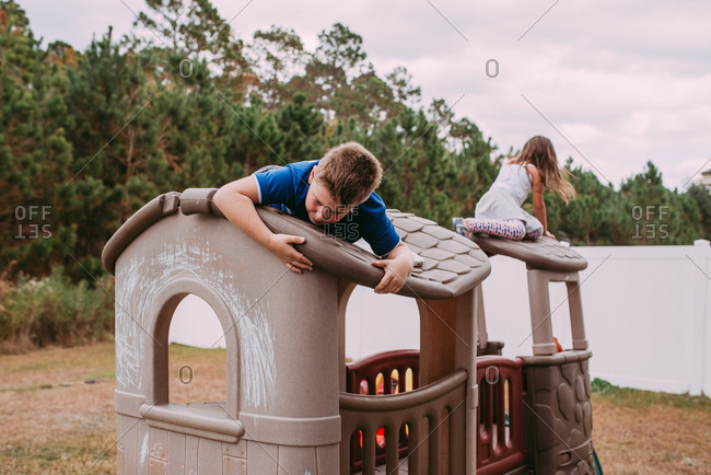 Young siblings play on top of toy house climbing structure