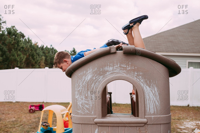 Boy lying on roof of play house in backyard