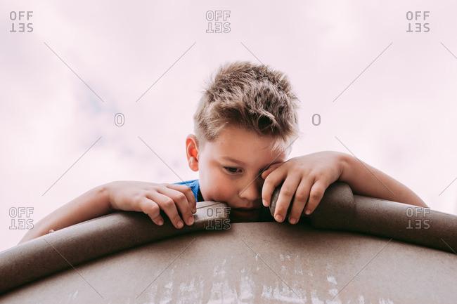 Boy lying on peak of toy house roof