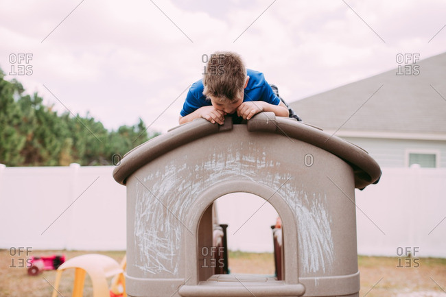 Boy lounging on the roof of a toy house