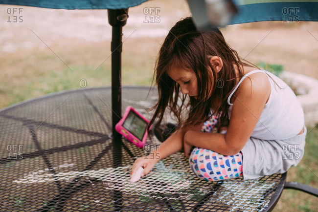 Young girl drawing with chalk on backyard table