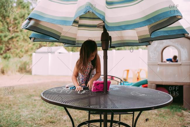 Girl drawing with chalk on backyard table