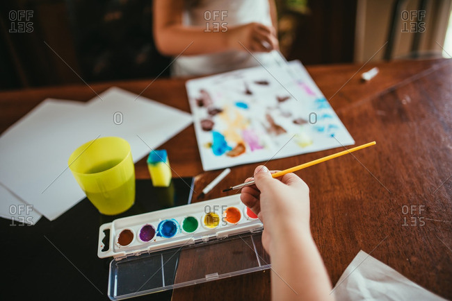 Children painting with watercolors at table