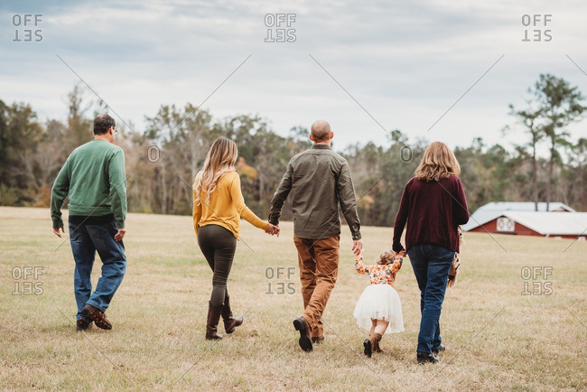 Back view of family walking together in field