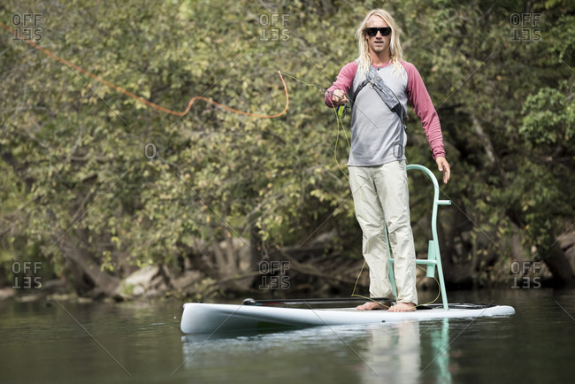 A Man Makes His Cast Directly At The Camera While Fly Fishing On His Paddleboard
