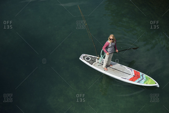 High Angle View Of Man Fly Fishing On His Paddleboard