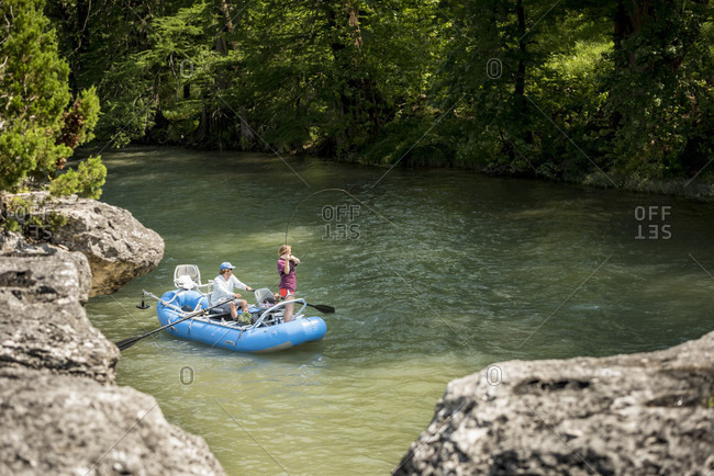 A Woman Fly Fishing For Rainbow Trout While Man Riding Dinghy On Guadalupe River