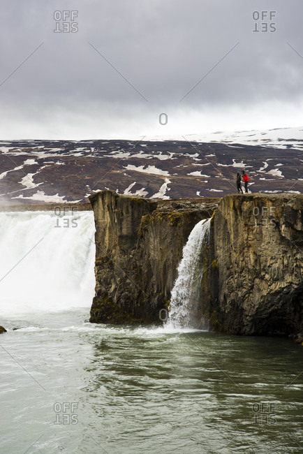 Tourist Exploring Godafoss Waterfall In Northern Iceland