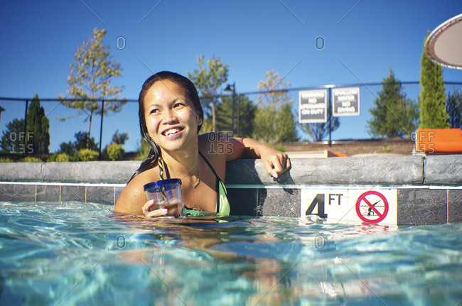 Smiling Asian Woman With Her Drink In The Pool