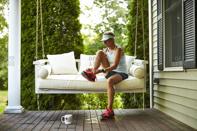 A Female Runner Sitting On Her Porch Swing Laces Up Her Running Shoes