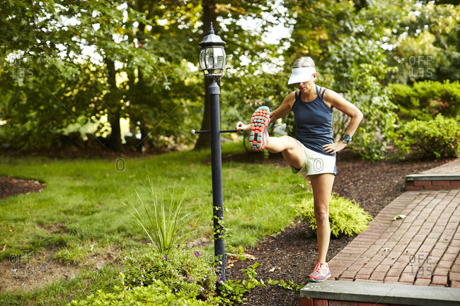 A Female Runner Stretches Before Her Run On A Lawn