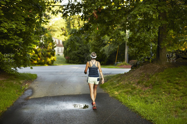 A Female Runner Heads Down The Driveway On The Way To Her Run