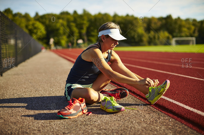 A Woman Changes Shoes Before Her Track Workout