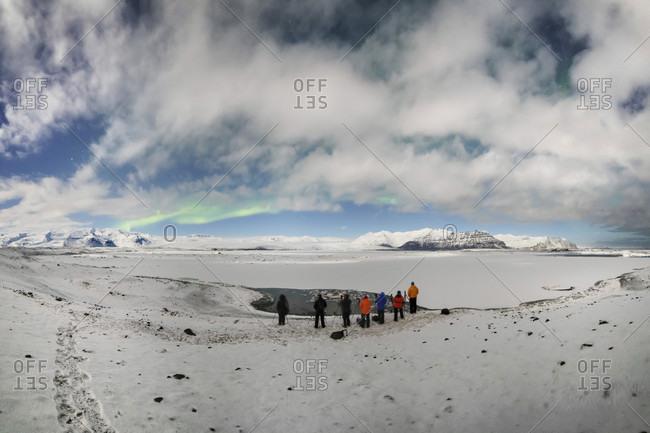 Photographers Exploring Aurora Borealis On Snowy Landscape In Jokulsarlon, Iceland