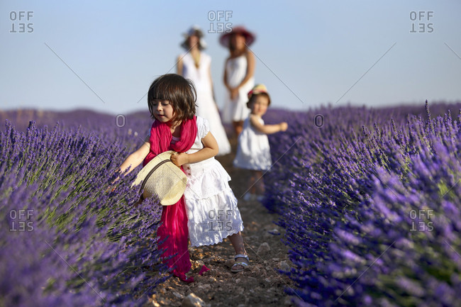Small Girl Playing With Purple Flowers Growing In Field