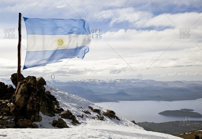 The Argentine Flag Blows In The Wind At The Top Of Cerro Catedral On A Sunny Day In The Andes