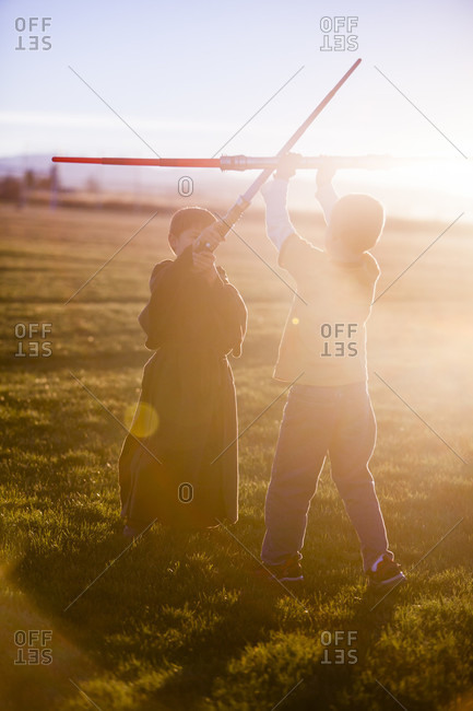 Two Boys Playing Sword Fight In A Field At Sunset
