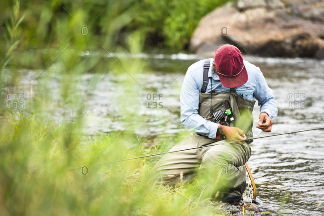 A Fly Fisherman Prepares His Gear While Sitting Next To The Yampa River, Colorado.