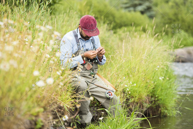A Fly Fisherman Prepares His Gear While Sitting Next To The Yampa River, Colorado