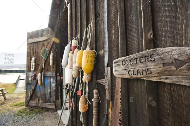 Buoys And Other Gear Hangs On A Wood Barn At A Shellfish Farm On Orcas Island