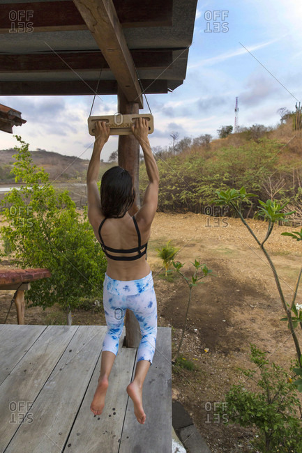 A Strong Female Hangs From A Hang Board On A Deck In Nicaragua