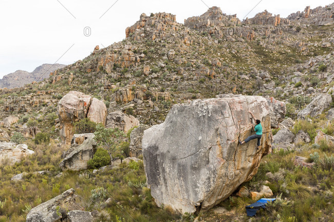 A Male Athlete Climbing A Tall Boulder In The Cederberg Mountains Of South Africa