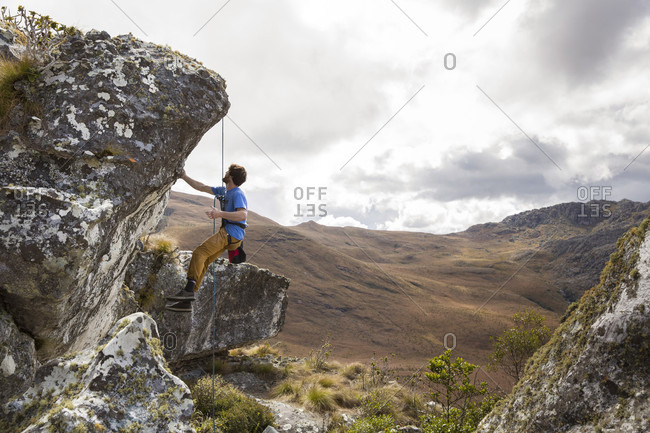 A Male Climber Looks At A Climb And Tests The Quality Of The Rock While Hanging From A Rope