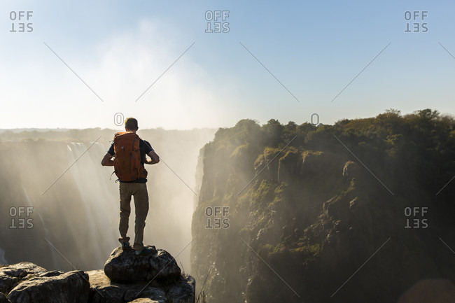 A Man Standing On Rock Exploring Victoria Falls In Zimbabwe