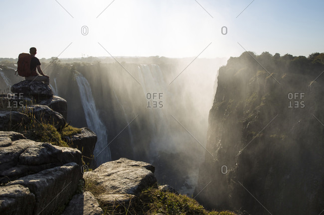 A Hiker Sits And Watches Victoria Falls In Zimbabwe
