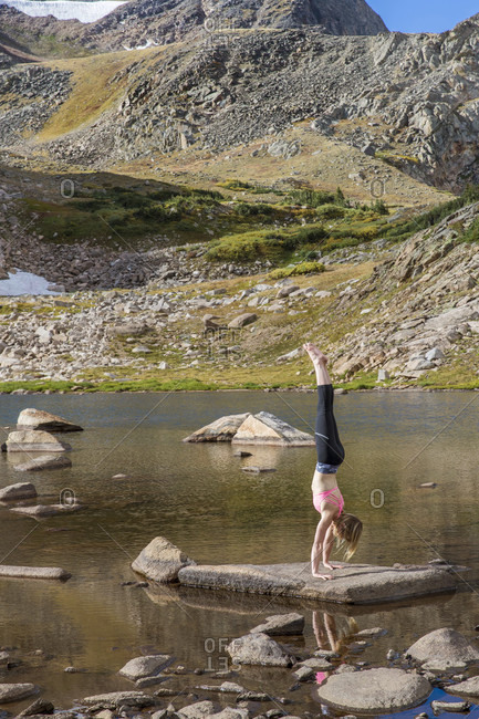 A Young Fit Woman Practices Yoga On A Lake In The Colorado Wilderness