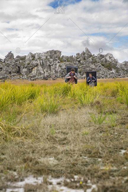 Two Climbers Hiking Through A Field With Crash Pads In Chimanimani National Park