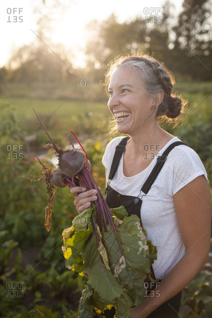 Happy Woman Holding A Clump Of Freshly Picked Beets From Her Garden In Fort Langley