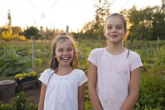 Portrait Of Two Sisters Laughing In The Garden In Fort